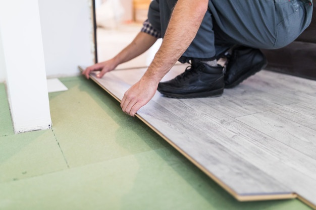 worker-processing-floor-with-laminated-flooring-boards_231208-4211 (1).jpeg
